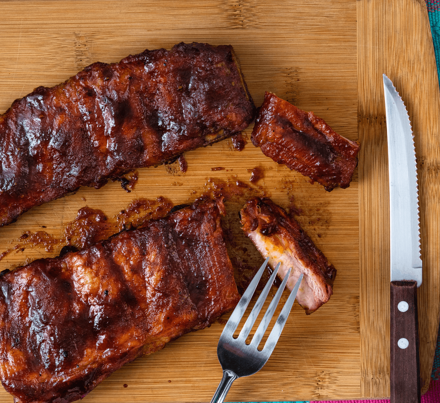 Candied pork ribs on a cutting board with knife and fork.